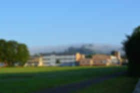Beaminster School on a sunny day with blue sky and a bank of fog