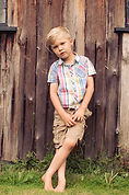 boy standing against a wooden wall - lifestyle portrait photographer