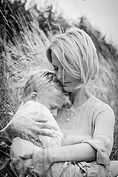 mother and son cuddling in a wheat field
