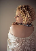 lady with curly hair looking over her shoulder - boudoir photography portraits\