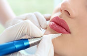 Young woman having permanent makeup on l
