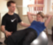 personal trainer helping with swiss ball situps