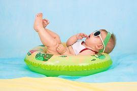 Bébé sur un bouée avec des lunettes de soleil