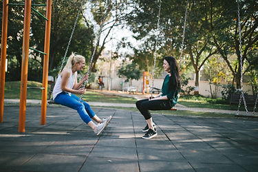 Image by Bewakoof.com Official blonde female brunette female sitting across from each other on swingset talking smiling laughing outside