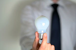 Stock image of a male holding a lightbulb in his hand.