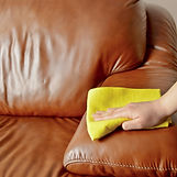 cleaning-brown-sofa-with-a-yellow-cloth-