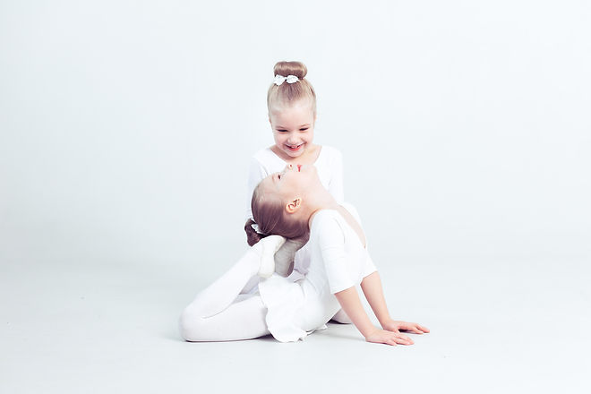 Little friends kids dancing ballet sitting on the floorand while smiling together in the modern danc