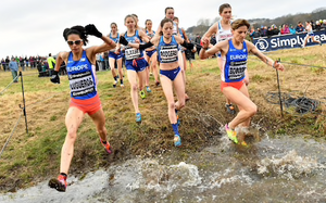 Picture of female cross country runners leaping a large puddle