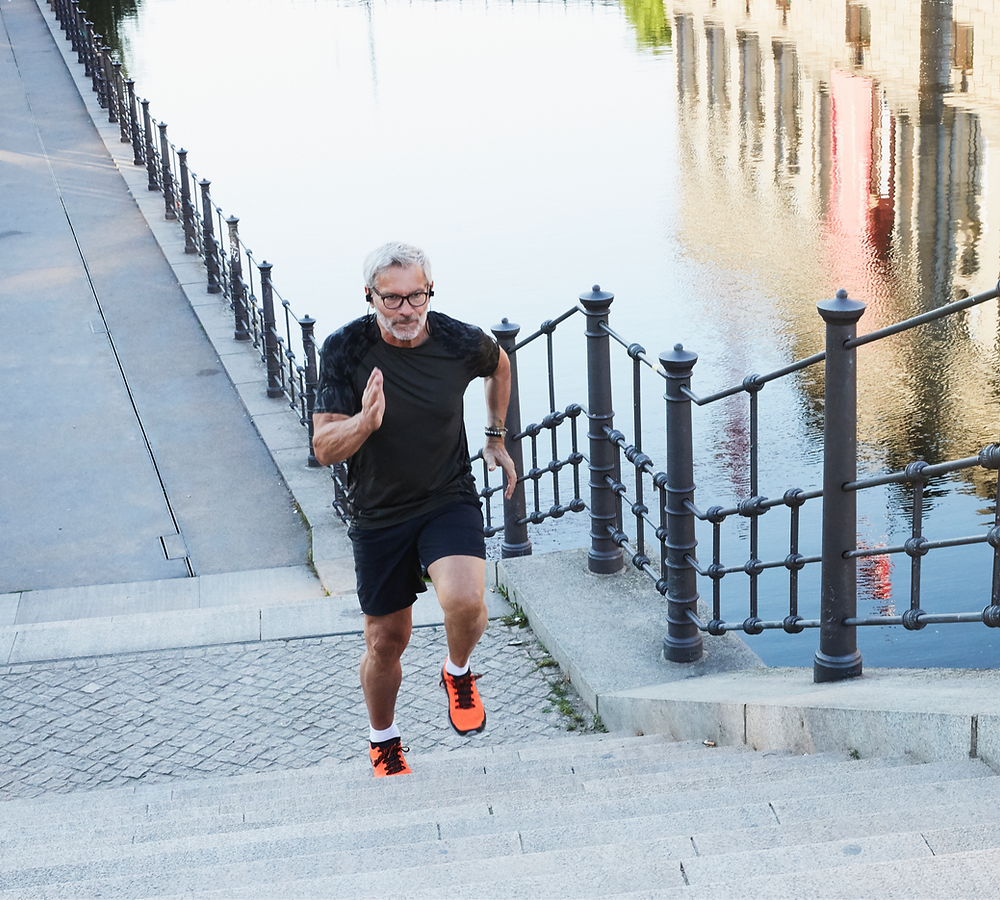 Man with grey hair running up steps by a river