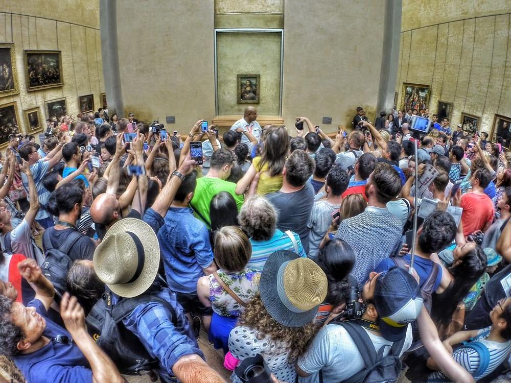 Crowds strain to catch a glimpse of Leonardo da Vinci's Mona Lisa at the Louvre in Paris. Photo by Max Fercondini, courtesy of Wikimedia Commons.