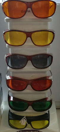 Image shows a display rack that holds 6 different overshield glasses with a variety of tints including; orange, amber, grey and yellow.