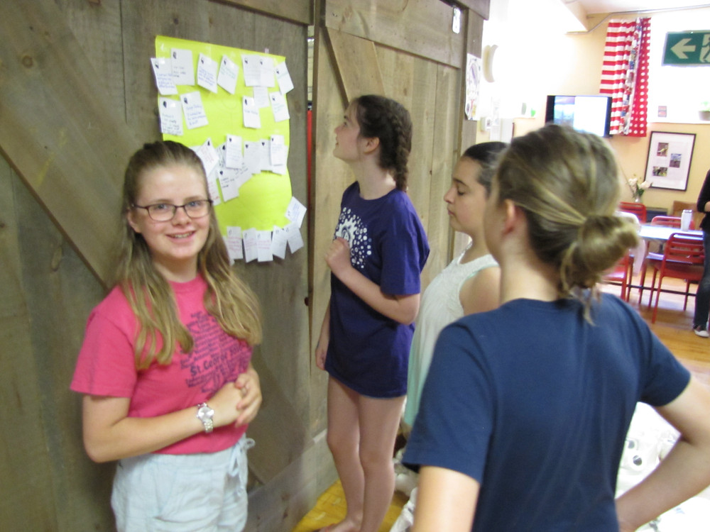 Four students add sticky notes to a wall-mounted note board.