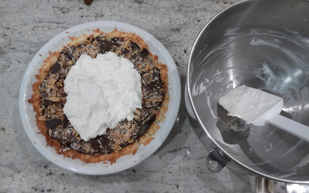 Coconut Cream Pie topped with whipped cream