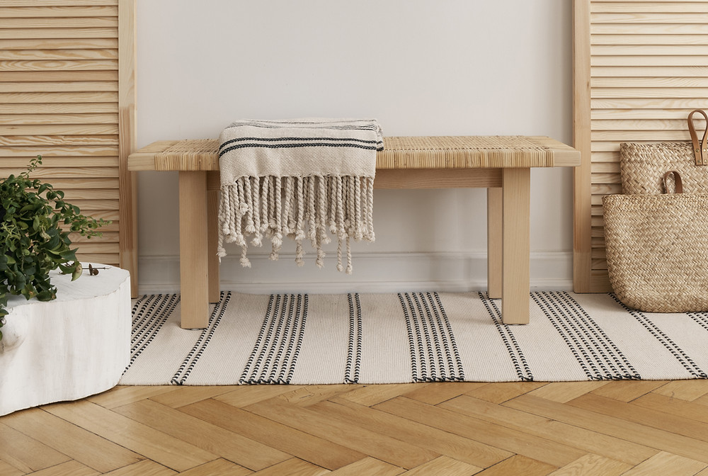 Woven striped rug under a bench