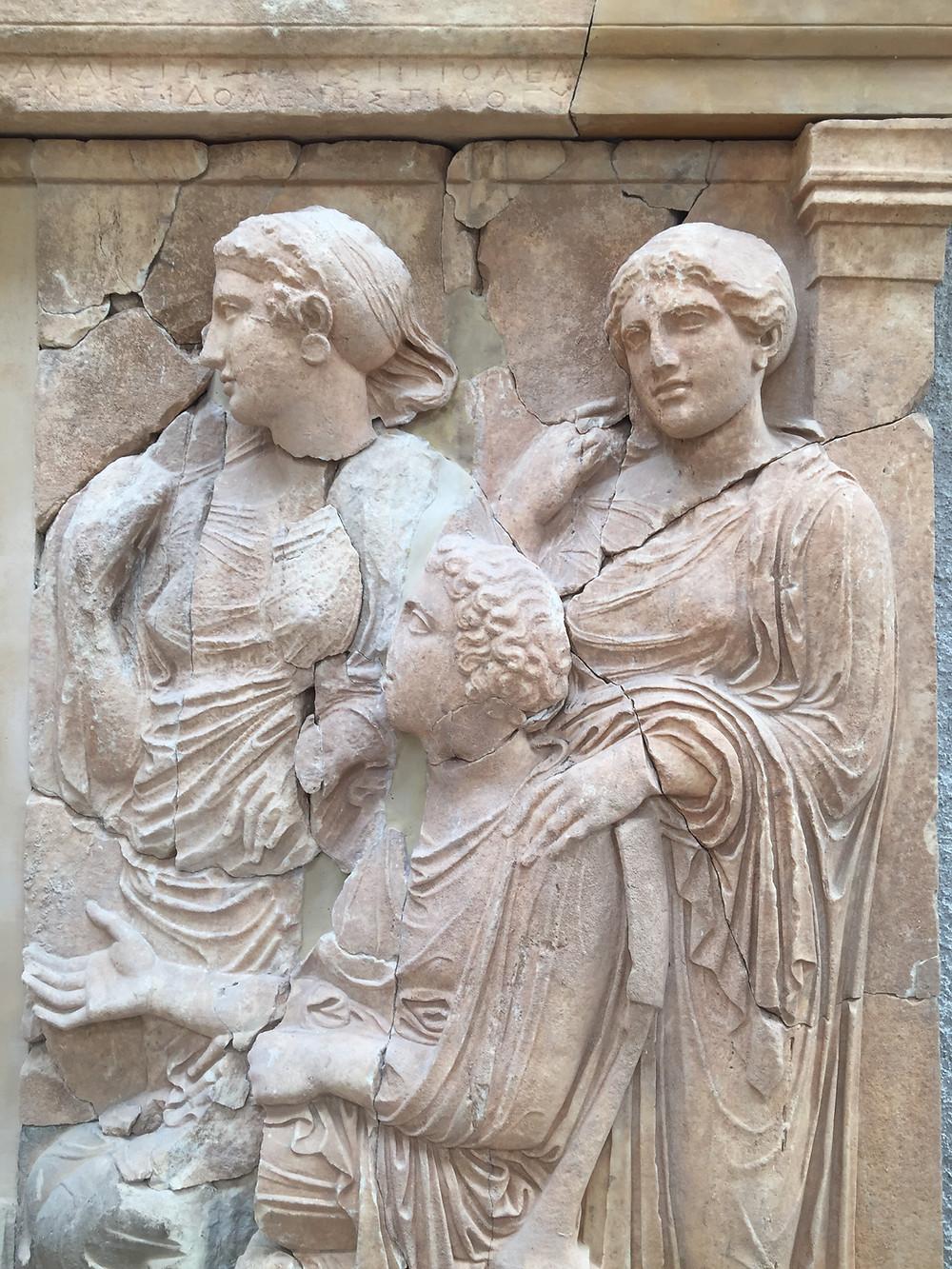 Λεπτομέρεια της επιτύμβιας στήλη της οικογένειας του Μενεστίδη. Απεικονίζονται 3 γυναίκες: οι δύο αδελφές και καθιστή η μητέρα τους, Ναυσιπτολέμη. Το έκθεμα βρίσκεται στην αίθουσα με το θριγκό του Ναού η οποία είναι επισκέψιμη κατόπιν συνεννόησης με την ΕΦΑ.