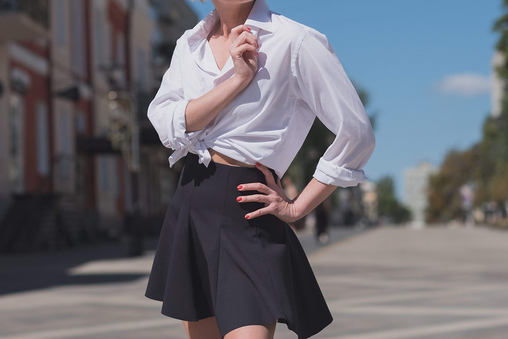Woman posing in a knotted white button-down shirt and flared black mini skirt.