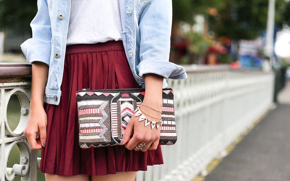 girl in dark red pleated mini-skirt holding zig-zag design beaded clutch