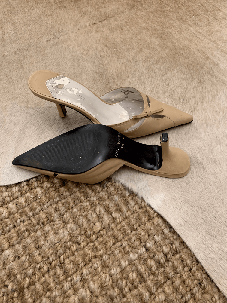 Old, destroyed high heeled shoes on a background of a jute carpet and cowhide rug.