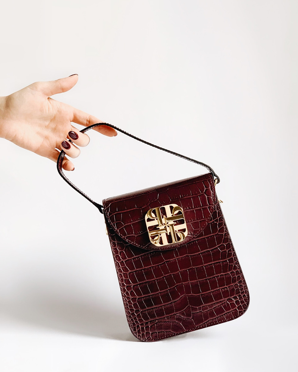 woman's hand with painted maroon fingernails holding a small, maroon crocodile-leather bag