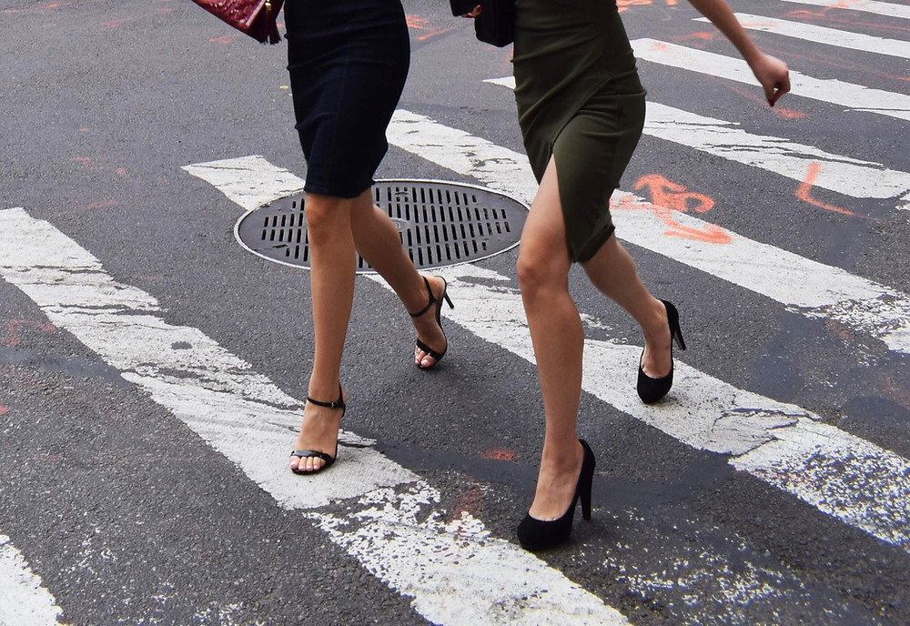 Two women crossing the street at the cross-walk, in black high heels and black skirts.