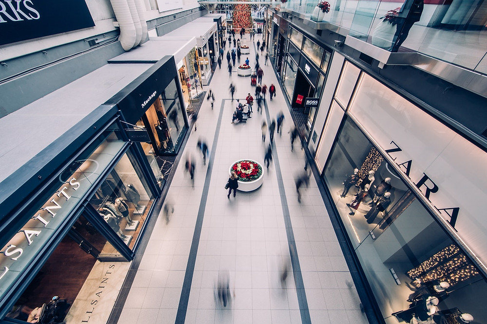 Blurred images of people walking through a mall, pictured from up high.