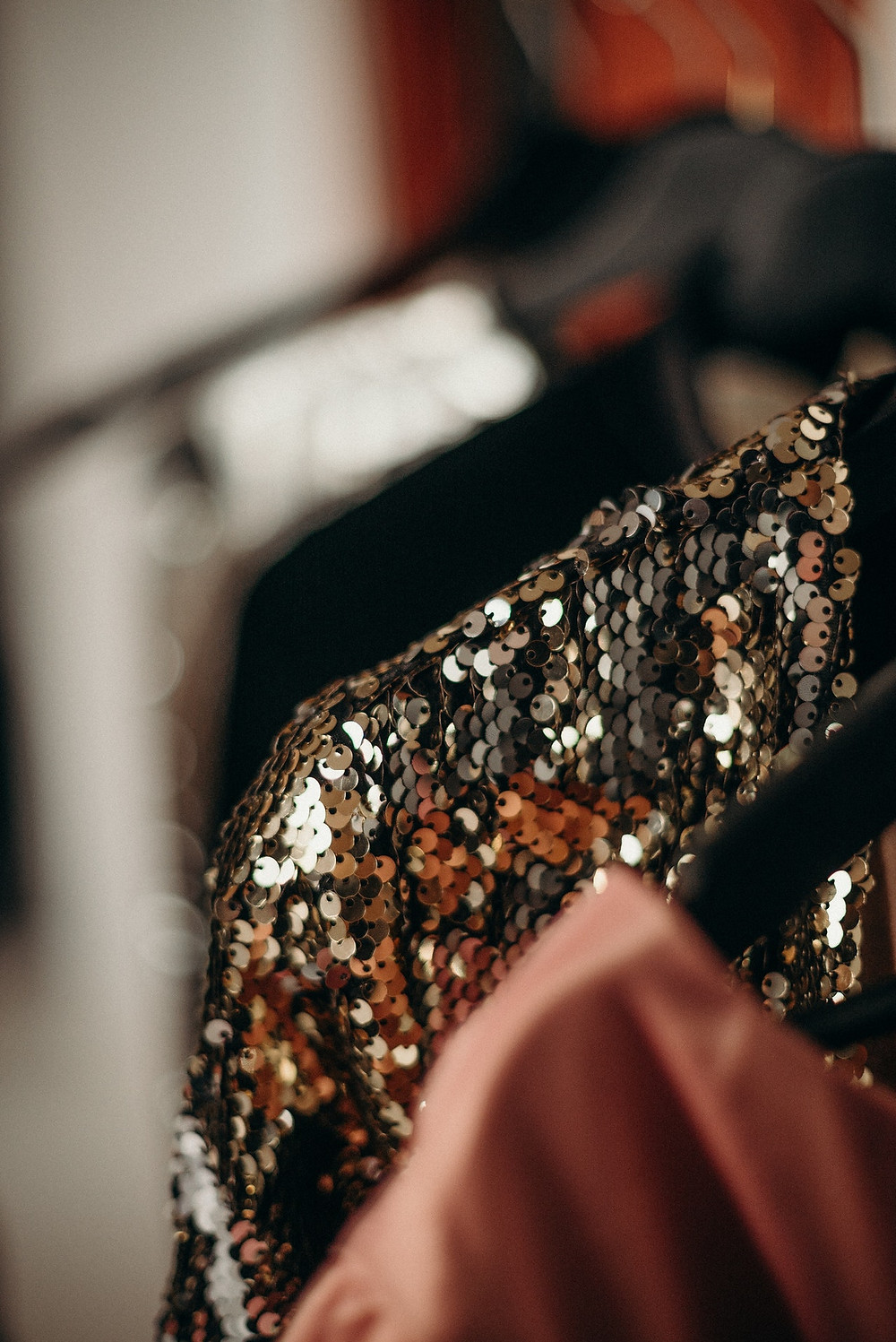 sequin jacket hanging on a hanger, with some other out-of-focus clothes hanging on hangers