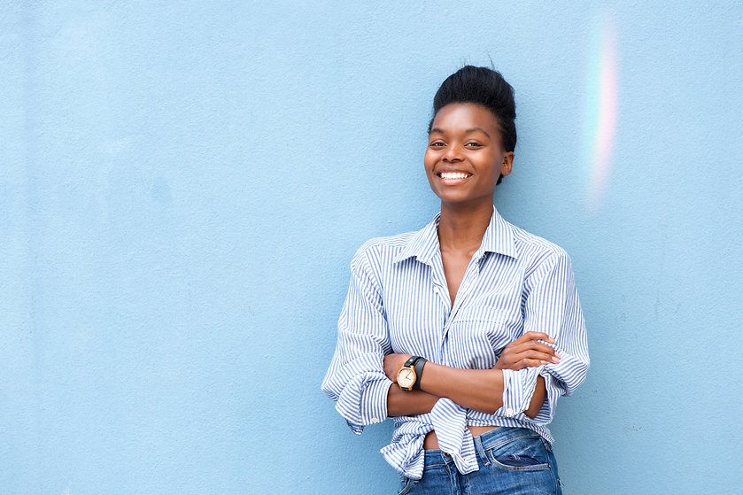 Portrait%20of%20african%20american%20woman%20smiling%20with%20arms%20crossed%20on%20blue%2