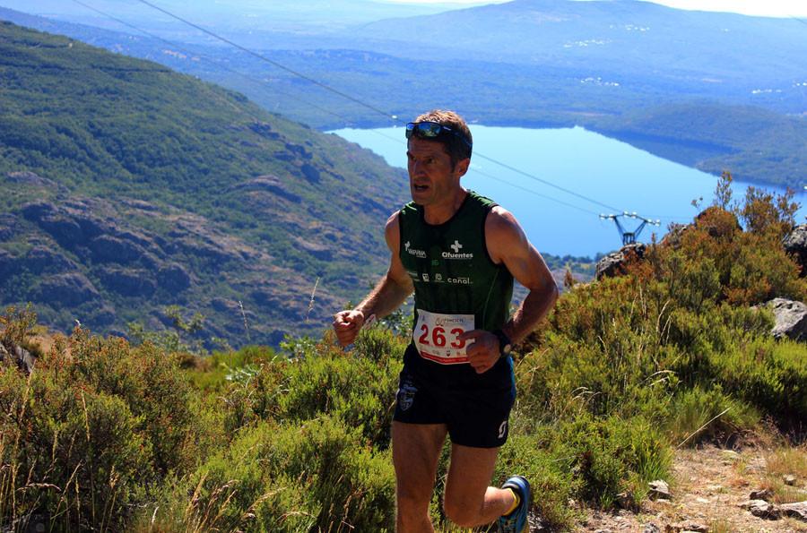 Un corredor, en la Carrera por Montaña  Fernando Casquero, con el lago de fondo.