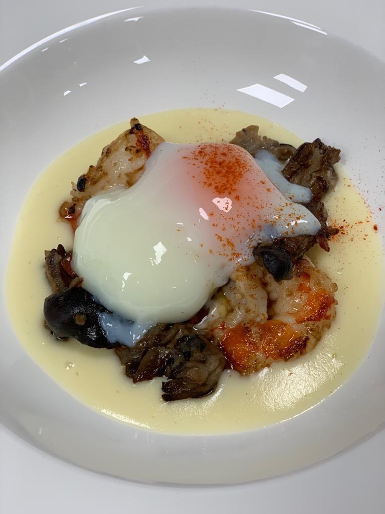 Huevo a baja temperatura sobre un guiso suave de cucurriles y langostinos.