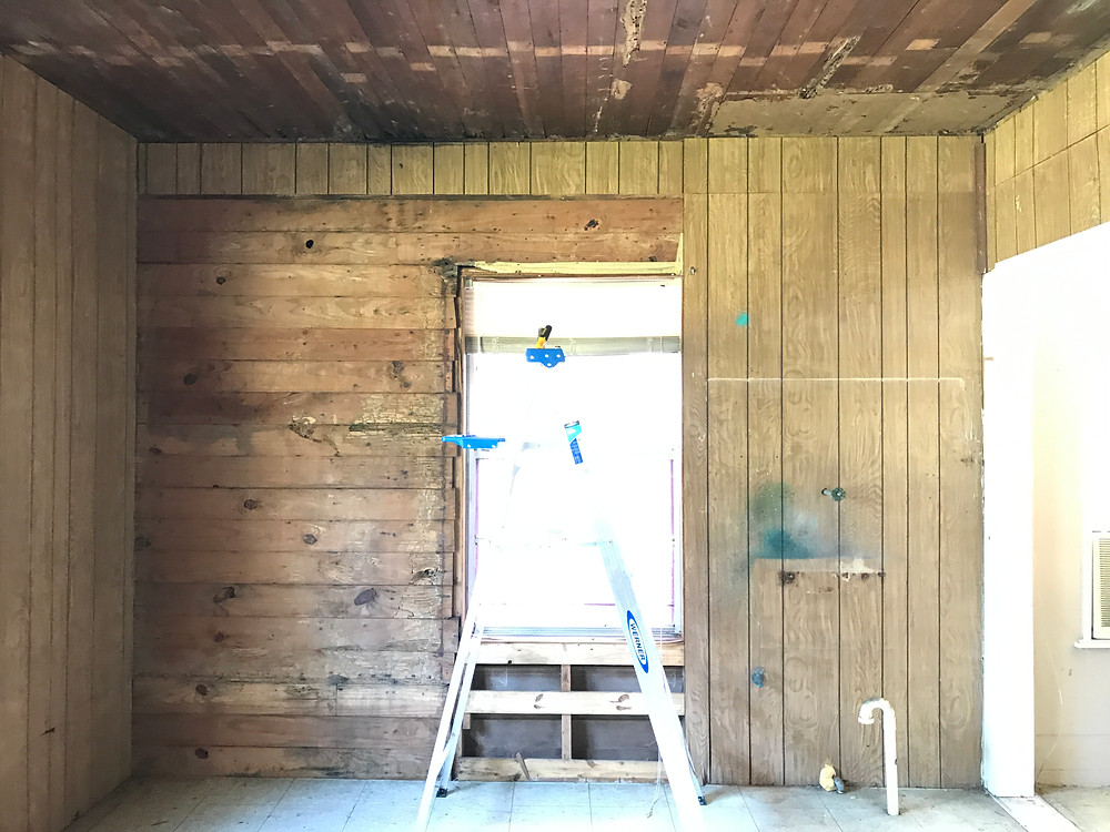 The old ceiling was pulled down and part of the paneling, exposing the tongue and groove wall.