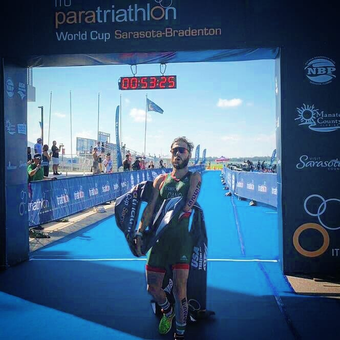 Juan Carlos Cano holding the finish ribbon after finishing first.  Instagram: @trimanitas
