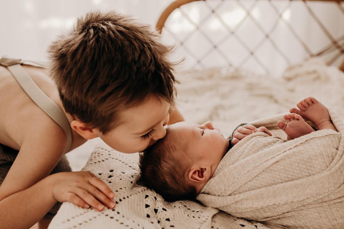 big brother kissing newborn-1.jpg