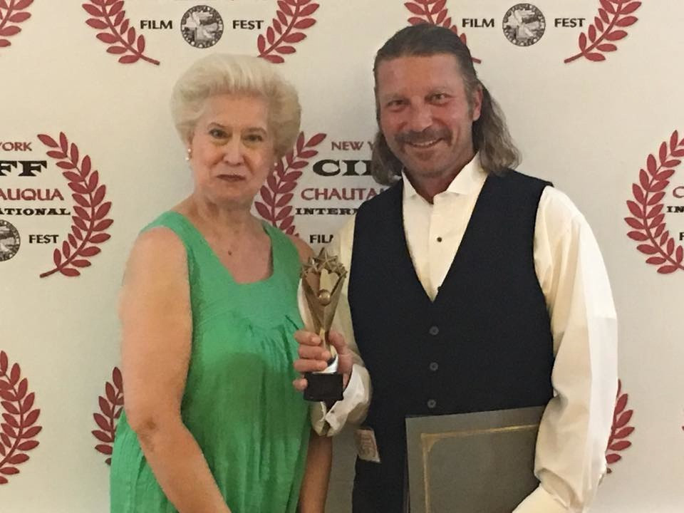 Festival Director, Diana Lenska, presents the award for Best Director (short film) to Karl Holtz on behalf of director, Bradley Hawkins.