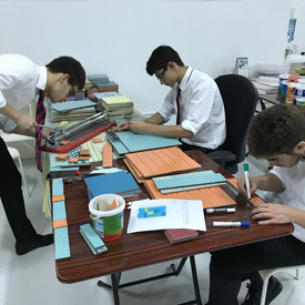 High school students help to cut tiles.