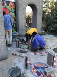 Installing mosaic stepping stones.