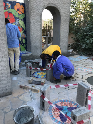 Installing mosaic stepping stones.