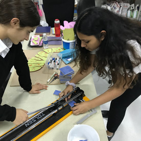Students learn to use a tile cutter.