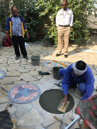 Installing a mosaic stepping stone that was created during an ealier art workshop.