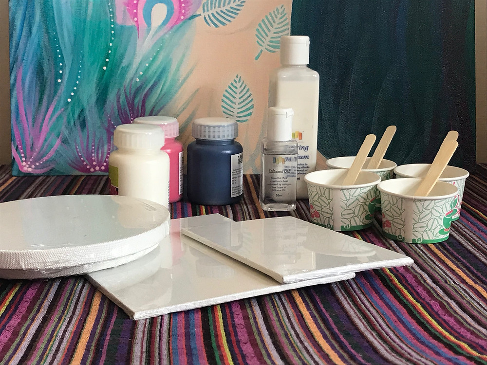 Paper cups with paint, small blank canvases, jars of acrylic paint, pouring medium, silicone oil and popsicle sticks