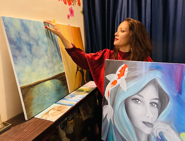 A photograph of Leeza A. Harris with her paintings