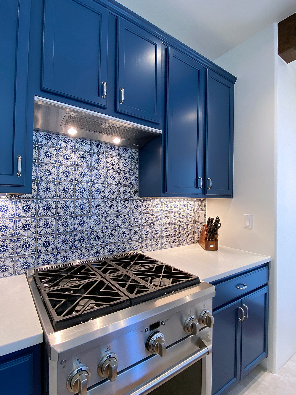 Bright blue kitchen cabinets with patterned blue tile in modern kitchen remodel
