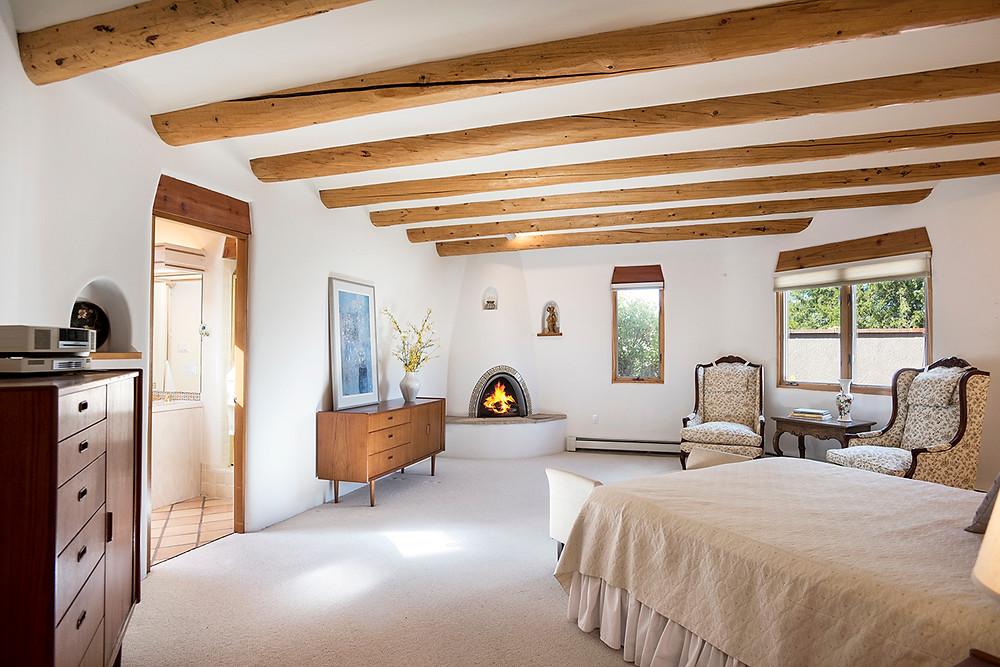 Southwest-style master bedroom with corner kiva fireplace