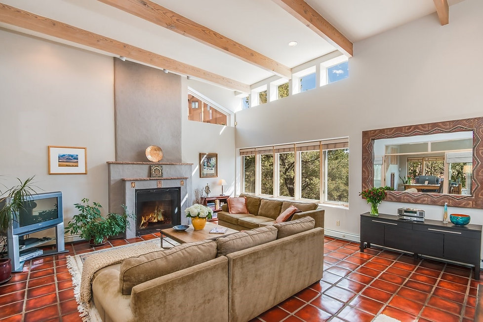 Bright red tile floor adds drama to New Mexico living room, complimenting natural light and neutral white walls.