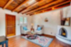 Charming traditional Santa Fe adobe living room with nicho and kiva fireplace.