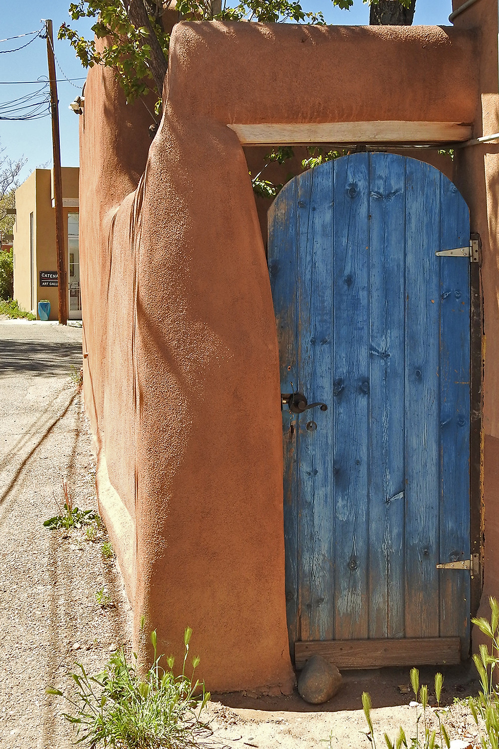 Weathered wooden gate painted blue in an adobe wall in Santa Fe, New Mexico