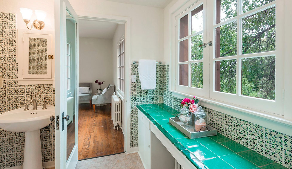 Bathroom with vintage decorative tile work and fresh flowers.