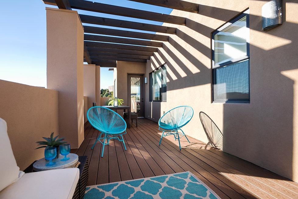 Sleek turquoise patio chairs mimic geometry of shadows on sunny Santa Fe porch.
