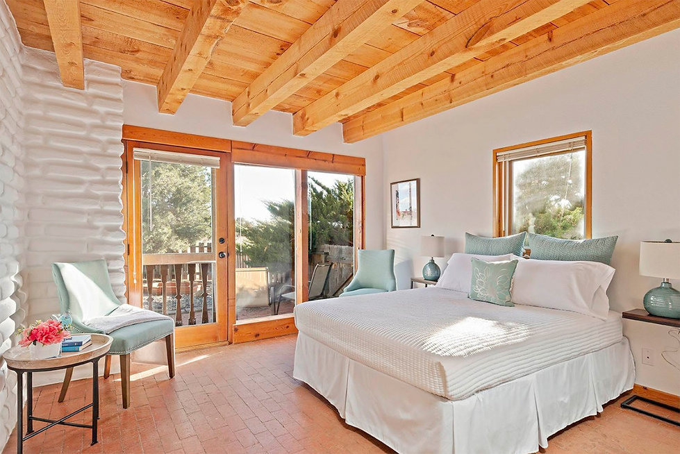 Classic and clean Southwest style in this El Dorado master bedroom complete with brick floors, vigas, and adobe walls.
