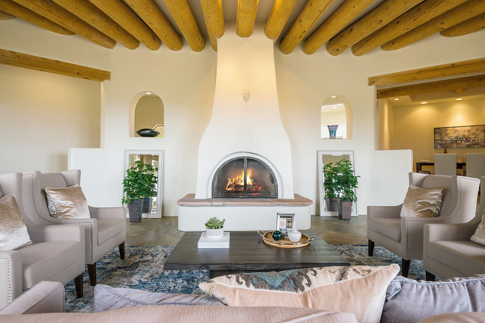A professionally staged formal living room with cathedral ceilings, vigas, and a central fireplace.