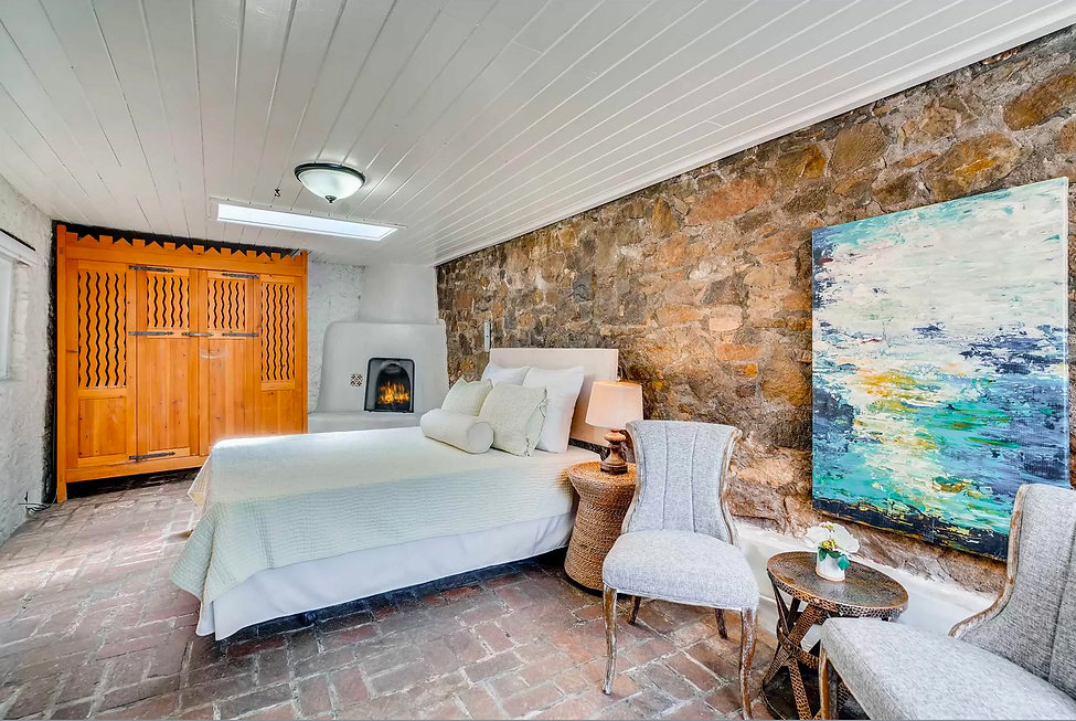 Traditional southwest style bedroom with river rock wall, seating area and wardrobe.